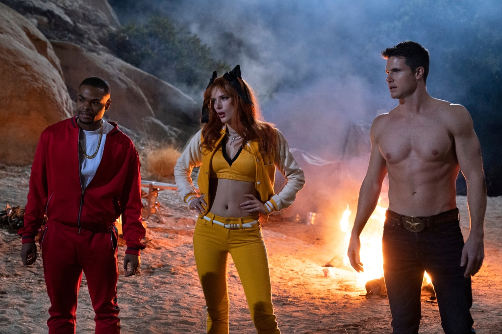A still from 'The Babysitter: Killer Queen'. John (Andrew Bachelor), Allison (Bella Thorne) and Max (Robbie Amell) stand in a desert, they are by a makeshift camp with a fire behind them. John is a Black man, in his 20s wearing a red tracksuit , white t-shirt and gold chain. Allison is a white woman in her 20s, red hair and wearing a yellow pair of jeans, bralet and letterman jacket., with black bows in her hair, she stands with her hands on her hips, confident. Max is the tallest of the 3, wearing jeans and no shirt, very physically fit, an all-american guy.