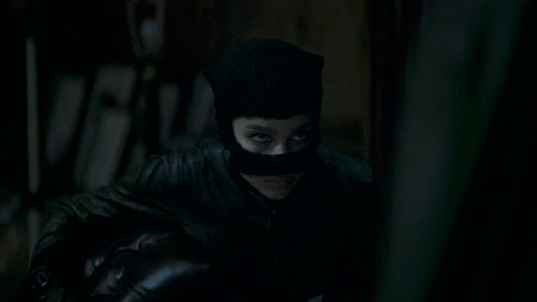 A still from the trailer for 'The Batman'. Catwoman (Zoe Kravitz) is shown in close-up in a very shadow drenched shot. She is a burglar, wearing a cat-like black balaclava and black leather jacket. She is crouching and looking up to an out-of-shot figure, she looks like she's just been caught.
