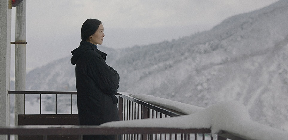 A still from 'The Calming'. Lin (Qi Xi) stands in a mid-shot on a balcony, shown in profile. The balcony is covered in snow and she looks out to shite-covered mountains and a grey sky. Lin is a Chinese woman, in her 30s, wearing a black parka jacket, her dark hair pulled back into a low pony tail, she looks reflective.