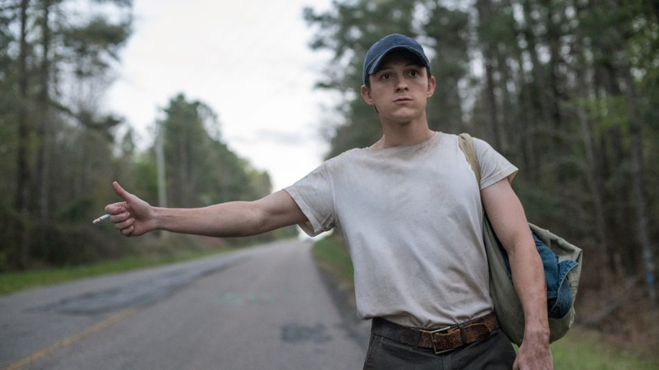 A still from 'The Devil all the Time'. Arvin (Tom Holland) stands on the side of the road, holding his thumb out to hitchhike. He looks unkempt and dirty, with a small satchel of belongings on his back. His white t-shirt is stained so much its turning grey, he has grey trousers with a brown belt and a blue cap on his head. His outstretched arm holds a cigarette.
