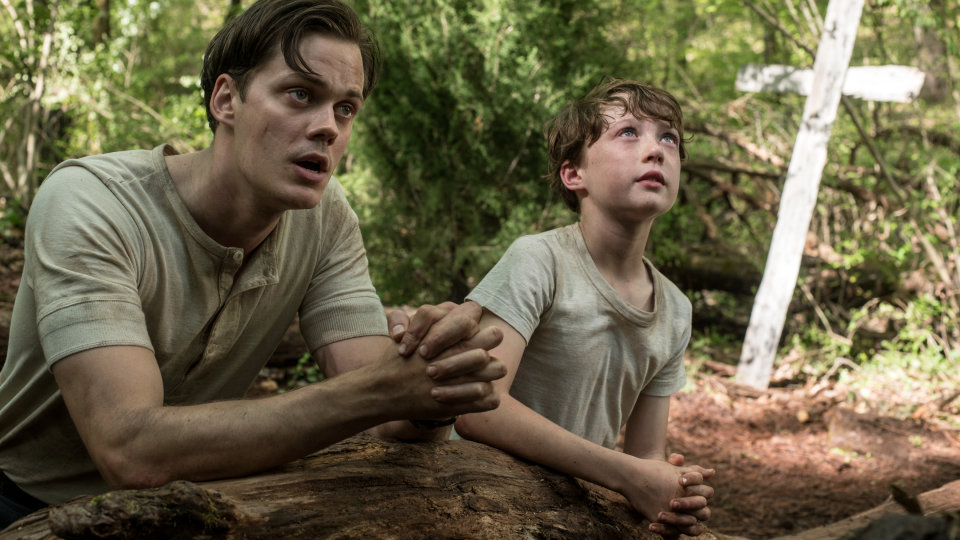 A still from 'The Devil all the Time'.  Willard (Bill Skarsgard) sits praying in a forest with a young boy, potentially a relative. They are kneeling behind a log, with their clasped hands resting on the log in prayer. A crucifix can be seen stood in the ground behind them. Both boys look sweaty and dirty, Willard even has a smear of dirt across his chiselled but gaunt face.