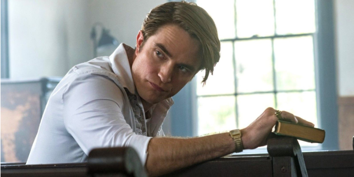 A still from 'The Devil all the Time'. Preston (Robert Pattinson) sits in a church pew, he is resting on hand the edge of the pew holding a Bible. He is looking behind over his shoulder. He has a crisp white tuxedo shirt on with ruffles and a gold watch on his wrist. His hair is dark blonde and greased to the side.