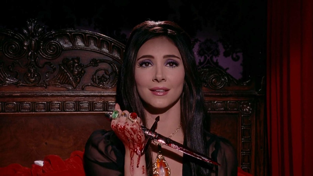 A still from 'The Love Witch'. Elaine (Samantha Robinson) sits against a dark wood headboard and purple ornate wallpaper. She has dark long hair and 1960s makeup. She wears a big gold chain with a huge amber pendant and clutches a bloody dagger in her hand, her hand is also covered in blood and she wears a ring on every finger.