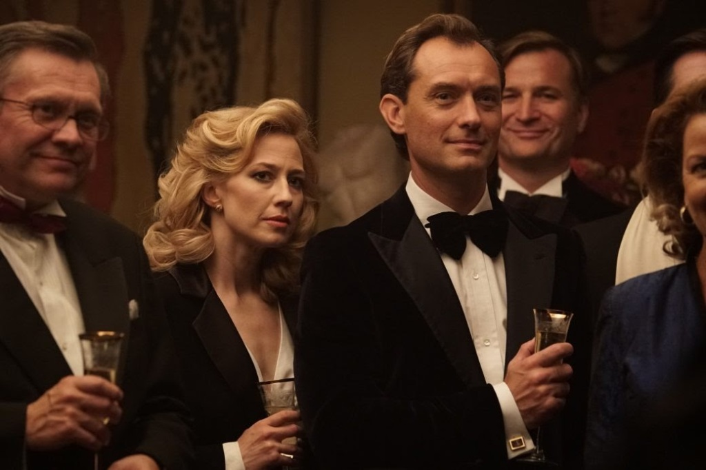 A still from 'The Nest'. Allison (Carrie Coon) stands at a formal function with husband Rory (Jude Law). They are both wearing black suits. Rory looks onward with a sense of satisfaction, whereas Allison looks unsure.