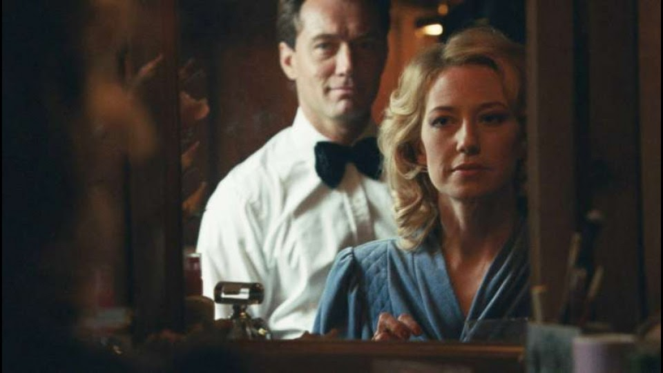 A still from 'The Nest'. Allison (Carrie Coon) looks at herself in the mirror, her husband Rory (Jude Law) is standing behind her. The image is a close-up view of the couple readying for a night out. It is 1980s set as you can tell by Allison's bouncy blonde curls and shoulder-pad clad blue dress. Rory wears a white dress shirt and black bow tie. He smirks at her and she has a expression of unease.