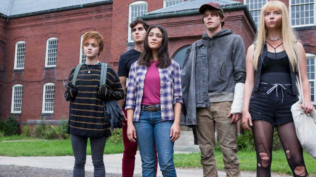 A still from 'The New Mutants'. Wolfsbane (Maisie Williams), Sunspot (Henry Zaga), Dani Moonstar (Blu Hunt), Cannonball (Charlie Heaton) and Magik (Anya Taylor-Joy) all stand outside of a psychiatric hospital. Wolfsbane is a tomboy in a baggy jumper and cropped hair and white skin, Sunspot is a handsome boy with dark hair and plain t-shirt and chinos, Dani Moonstar is an Indigenous young woman wearing a plaid shirt and jeans. Cannonball looks like a bit of a redneck, with scruggy clothes, scruggy hair and a baseball cap. Magik has something smeared on her face, long blonde hair and all black, short clothes.