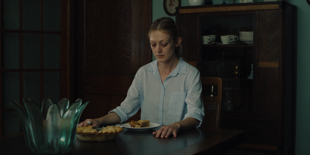 A still from 'The Swerve'. Holly (Azura Skye) sits in a darkened dining room at the head of the table, alone, staring down at the slice of Pie she has cut herself. Her hands lay on the table as if she is stressed, she looks tired.