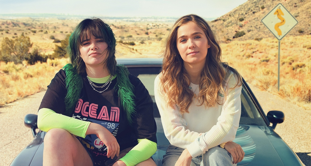A still from 'Unpregnant'. Bailey (Barbie Ferreira) and Veronica (Haley Lu Richardson) are sat on the hood of a car out in the middle of the desert road. Bailey has her elbow resting on her knee, she has black shaggy hair with dark green running through it and a fringe. She has a black 80s style graphic tee on with a neon yellow long sleeve underneath and two silver chain necklaces on her neck. Veronica is much plainer, long blonde wavy hair, minimal makeup and a plain white jumper on.