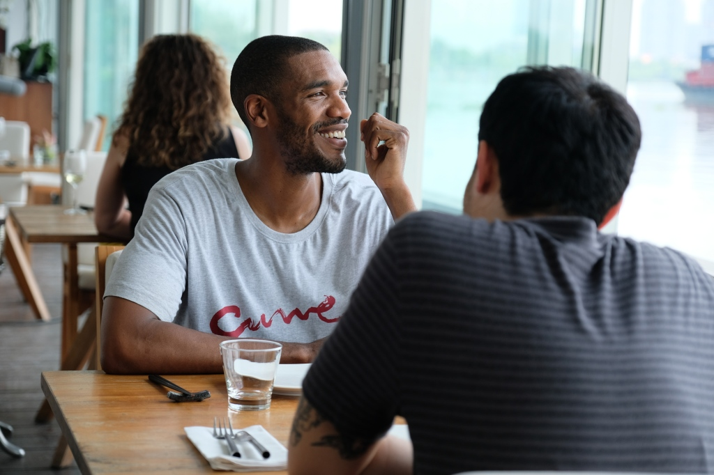 A still from 'Monsoon'. Lewis (Parker Sawyers, a 30-something African-American man, is shown chatting in a restaurant to Kit (Henry Golding), who we can only see from behind. The image is shot over Kit's shoulder. Lewis looks out of the window, smiling as he talks.