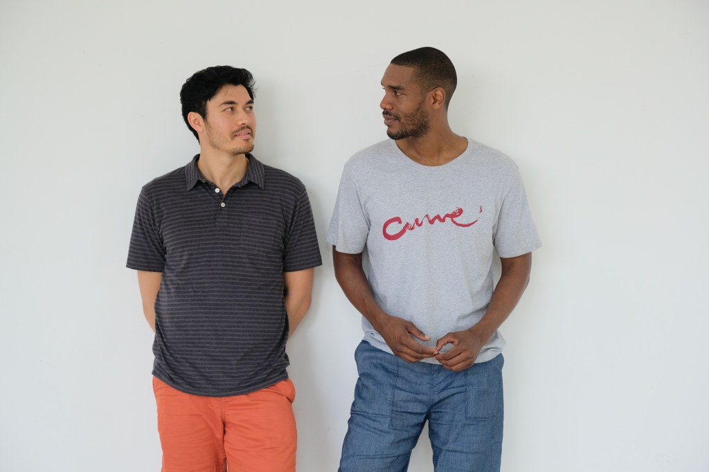A still from 'Monsoon'. Kit (Henry Golding) a 33 year old Vietnamese-British man stands against a white wall next to Lewis (Parker Sawyers), a similarly aged African-American man. Kit is listening to Lewis talk. Kit wears coral coloured shorts, and a grey striped polo shirt. Lewis wears jean shorts and a grey t-shirt with 'Curve' written across the front in red lettering.