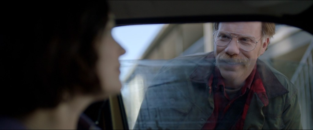 A still from 'Alone'. The Man (Marc Manchaca) is shown in close-up peering through the cracked window of Jessica's (Jules Wilcox) car. Jessica can be seen just out of focus to the left of the image, staring at the Man. The Man has a handlebar moustache, strawberry blonde hair and aviator style reading glasses, he is wearing a lot of layer including a plaid shirt and a khaki jacket.