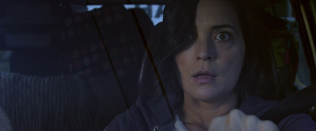A still from 'Alone'.Jessica (Jules Wilcox) is shown in close-up, the image shot through her car windscreen. She is staring through the camera in fear, her mouth agape and hand on the wheel. She is a 30-something white woman with chin-length black hair, covered one of her eyes.