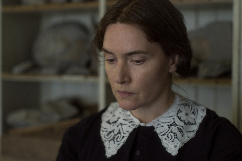 Still from Ammonite. Kate Winslet in close up, looking down to the bottom left of the camera. She has her hair tied back and is wearing a white lace collar.