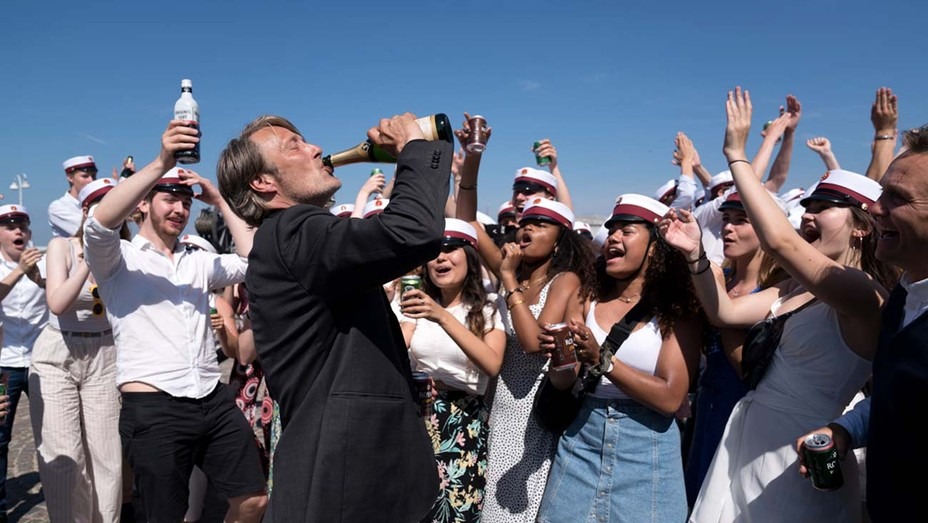 A still from 'Another Round'. Martin (Mads Mikkelsen) is stood in a suit drinking a bottole of champagne in front of a crowd of studnets, most of them wearing sailors caps. The students are cheering him on and raising their glasses to him as the bright sun beats down.