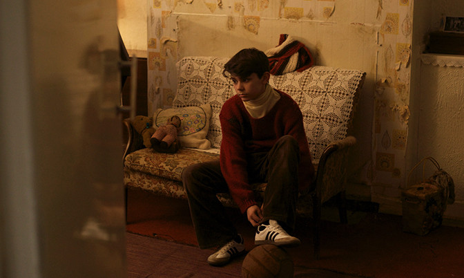 A still from short film 'Antonio'. A young boy is shot through a doorway into a living room, he is sat on a sofa tying his shoelaces, looking vacantly across the room. The film is 1970s set and in Scotland, the decor absolutely reflects an outdated and grim way of living. Antonio himself wears brown corduroy trousers and a red jumper with polo neck jumper underneath. His Adidas trainers are brand new, and this newness is in direct contrast with the peeling wallpaper in his home.