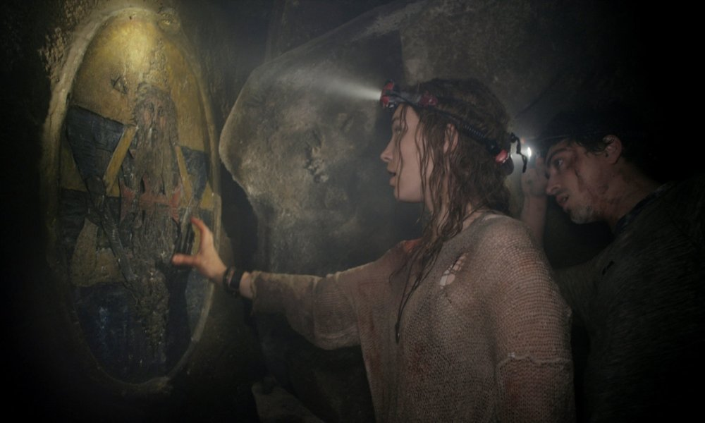 A still from 'As Above, So Below'. Scarlett (Perdita Weeks) is shown in a mid-shot profile view examining a cave carving/painting deep in the catacombs. She is flanked by another researcher who stands behind her, giving her additional light to view the carving with his headtorch, as well as her own. Her long hair is wet and her brown jumper looks ragged, she is reaching out to touch the carving.