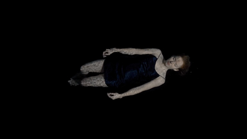 A still from short film 'Asphyxiate'. The image is doused in black and a woman is shown centre frame, horizontally, it is as if she is floating in a sea of black. The woman is young white and very pale, wearing a black nightdress, her eyes are closed.