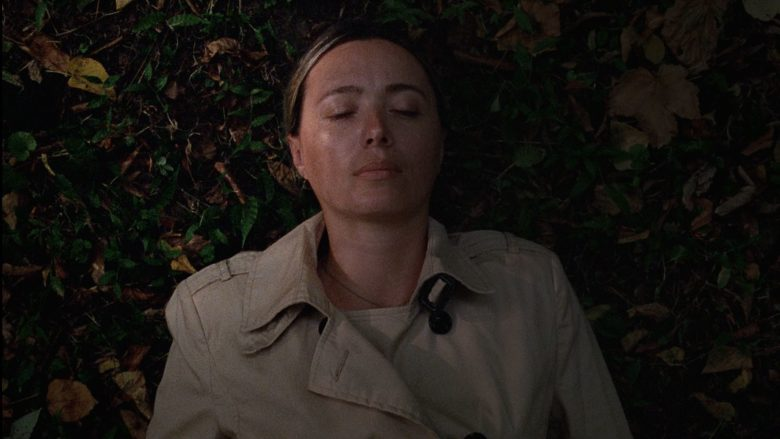 A still from 'Beginning'. Yana (Ia Sukhitashvili) is shown in close-up, laying on the floor in a pile of leaves. Her eyes are closed, she wears a beige trenchcoat and has her blonde hair slicked back off her face.