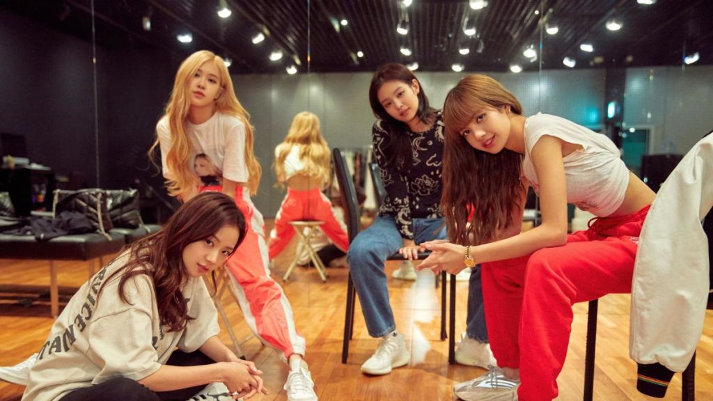The K-Pop girl group 'Blackpink' pose for a promotional shot in a dance studio.