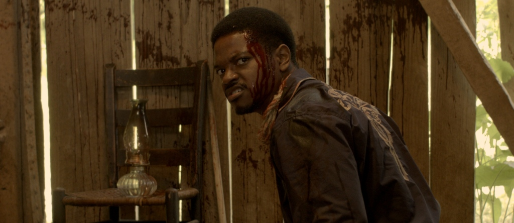 A still from 'Death Ranch'. Clarence (Travis Cutner) is shown in close-up, centre frame. He is crouched side on, turning his face towards the camera in a disgusted grimace. He is a young Black man with short hair and a moustach/goatee. He wears an embroidered 70s shirt and the left side of his head is covered in blood. He is inside a barn, next to him is a wooden chair with an oil lamp on top.