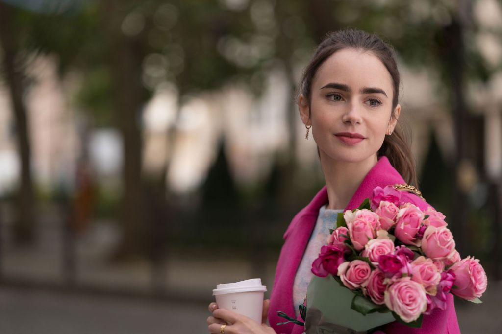 A still from 'Emily in Paris'. Emily (Lily Collins) is shown in a head and shoulders shot, to the right of the image, the background is blurred and she is the focus. She has very fair skin and brown hair in a ponytail. Her pink lipstick matches that of her fancy coat and the bouquet of roses in the crutch of her arm. She clutches a coffee cup also.