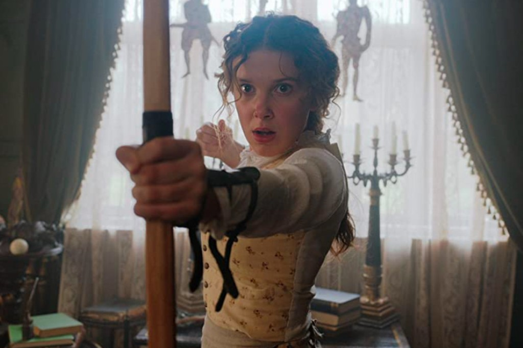 A still from 'Enola Holmes'. Enola (Millie Bobby-Brown) is shown in mid shot, centre frame in a late-Victorian living room. There are huge velvet curtains behind her, candlesticks and books scatter the scene. Enola is wearing a light yellow printed waistcoat and white linen undershirt and she plays with a bow and arrow. Her face is one of shock and her long brown hair is waves and pulled back into a ponytail.