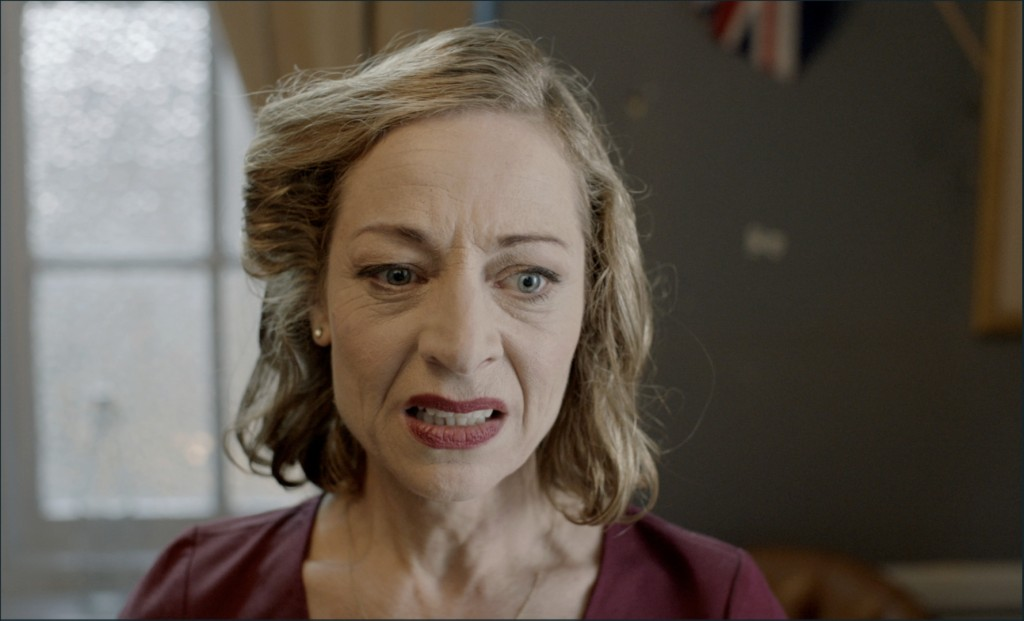 A still from short film 'Full English'. A women in her late 50s is shown in close-up, just off centre. She is a well dressed lady with curled and styled blonde hair, heavy makeup and a smart red dress that matches her lipstick. She is grimacing and looking down almost towards the floor.
