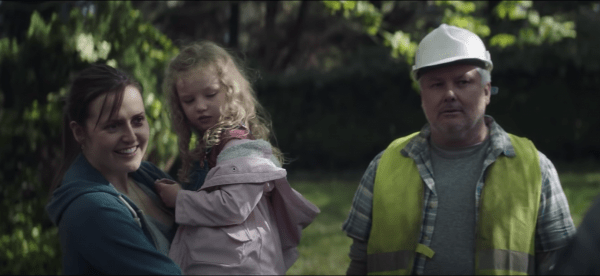 A still from 'Herself. Sandra (Clare Dunne) stands outside holding her daughter who is about 3 years old. She stands next to a man in construction gear, a high vis vest and hard hat. Sandra is smiling at someone else who is not shown in the image.