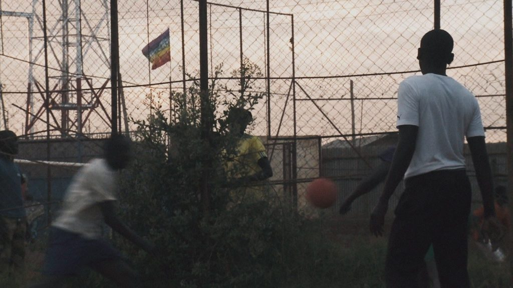 A still from documentary 'I am Samuel'. A young Kenyan man is the only figure standing still in this image. He stands to the right wearing black trousers and a white t-shirt, his back to the camera. He watches on over a group of friends playing with a ball. There is 3 other men in movement and one woman. It is nearing sunset in the landscape behind, and an electrical pileon can be seen to the left of the image, a Pride flag waves proudly in the distance