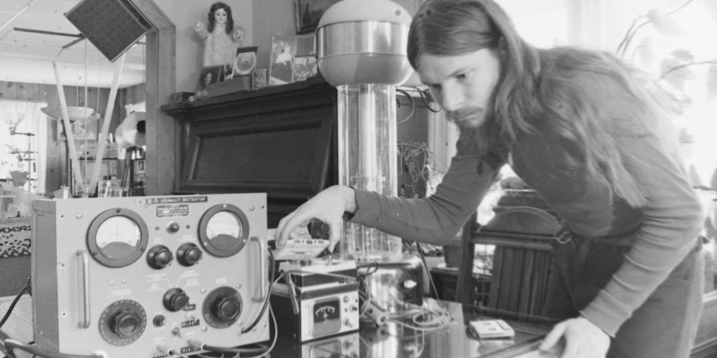A still from documentary 'John was Trying to Contact Aliens'. John Shepherd is seen working over a UFO detector machine in the living room of his parents' home/ The soft furnishings and 70s decor of the living and dining space are in direct contrast to the machinery and wires John is tampering with. John is leant over a table holding a cassette, he wears a polo neck jumper and has long hair and a full beard. The image is in black and white.