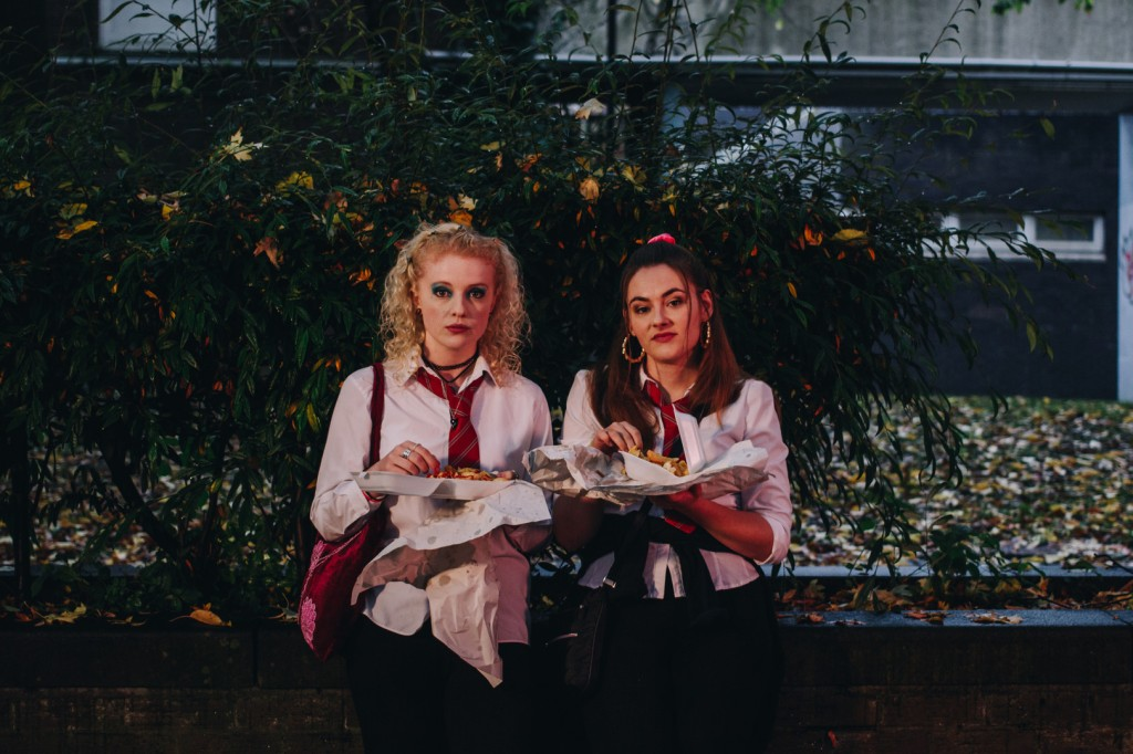 A still from short film 'Love Spell'. Two girls are shown centre frame, head to their knees. They are in school uniforms with messy ties and untucked shirts, their hair, makeup and bags show the film is set in the 90s: srucnhies, butterfly clips, bamboo hoops, excessive eyeshadow and tattoo chokers. The girls are eating fish and chips, standing against a wall and a small tree, staring directly at the camera.