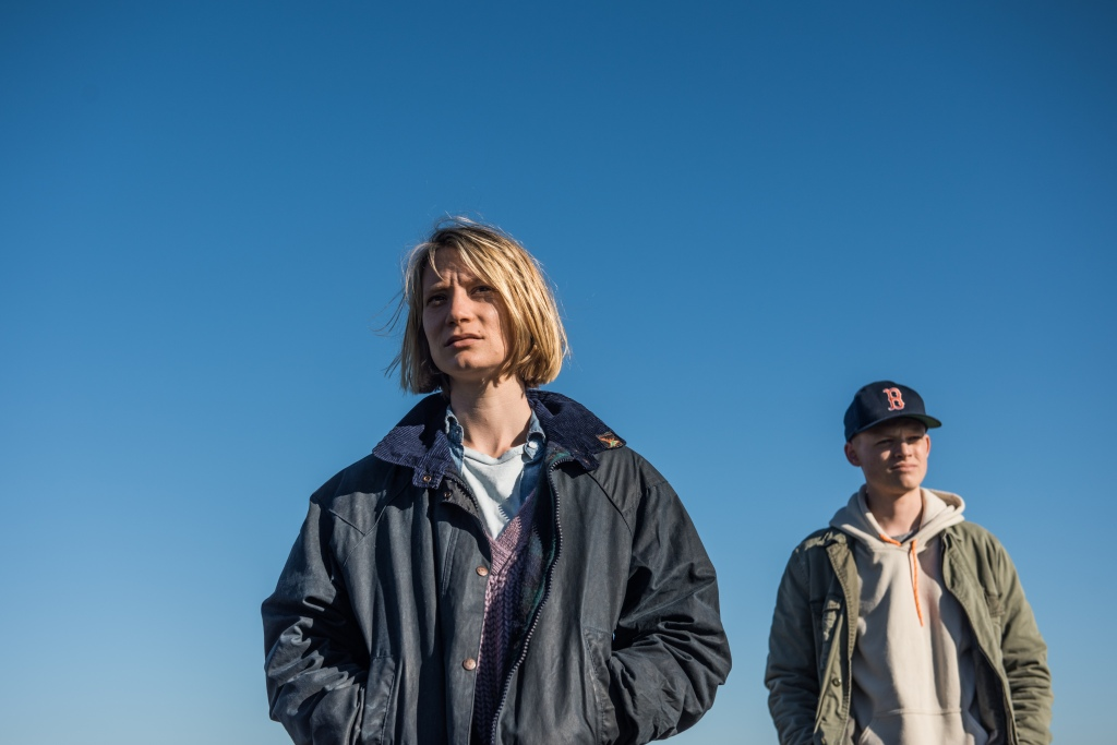 A still from 'Blackbird'. Anna (Mia Wasikowska) is shot from below in a mid shot so that the whole image is filled with blue sky. She is flanked on her right a boy who is wearing a hoodie and khaki jacket with baseball cap. Anna's face looks disgruntled and her hands are stuffed in the pocket of her oversized Barbour jacket. she wears purple knit jumper underneath and her blonde hair is cropped at the chin.
