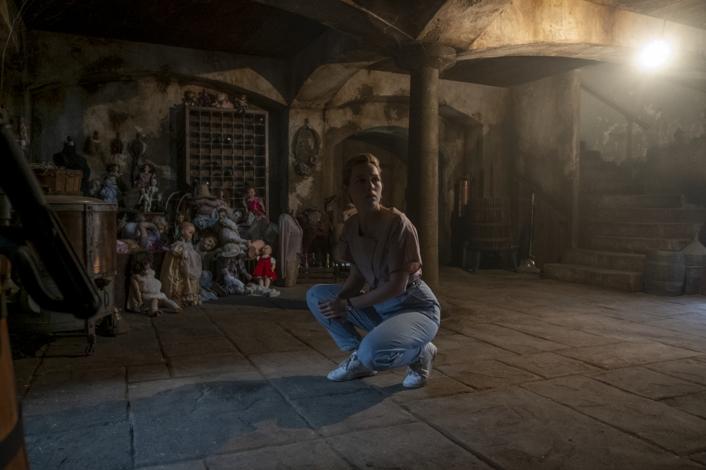 Victoria Pedretti as Dani Clayton in The Haunting of Bly Manor (2020). Dani, a young woman wearing a pink blouse and blue jeans of the 80s style, is crouches in a dimly lit basement, surrounded by strange objects including a pile of creepy looking dolls.