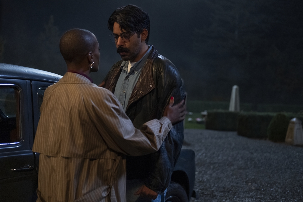 T'Nia Miller and Rahul Kohli as Hannah Grose and Owen Sharma in The Haunting of Bly Manor (2020). Hannah and Owen are stood on the driveway of the manor in front of a car, as Owen prepares to leave. Hannah holds Owen's arms, reassuring him, as he looks deeply sad.