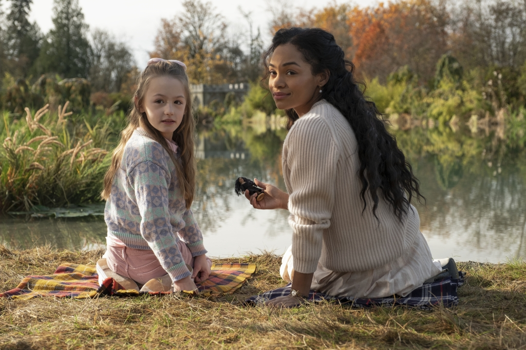 Amelie Bea Smith and Tahirah Sharif as Flora Wingrave and Rebecca Jessel in The Haunting of Bly Manor (2020). 8-year-old Flora and her nanny Rebecca are sitting on the grass in front of a large lake surrounded by trees. They both face the lake but look back over their shoulders to see something behind them. Rebecca is holding a small handmade doll.