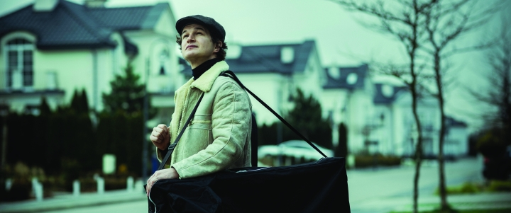 A still from 'Never Gonna Snow Again'. Zenia (Alex Utgoff) stands in midshot in the middle of a perfect suburban street during the start of winter. He is a masseuse, and carrying his fold up table on his shoulder in a bag. He wears a sheepskin cream jacket and flat top cap, he looks up towards the sky.