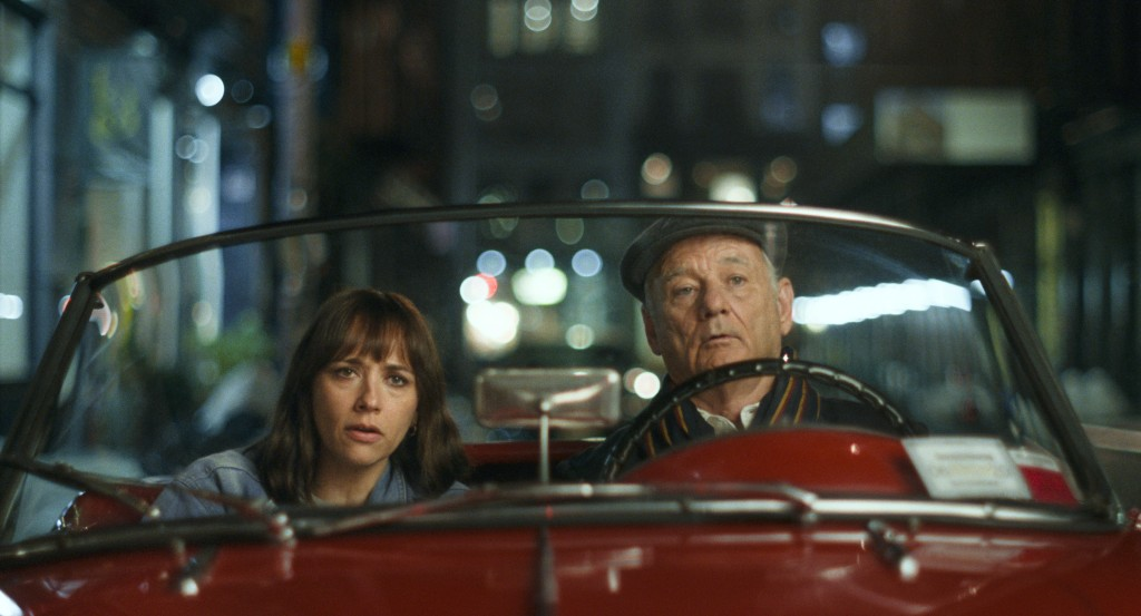 A still from 'On The Rocks'. Laura (Rashida Jones) sits in a red convertible with her father Felix (Bill Murray). The image is a closeup so you can only see the windscreen of the car and the blurred cityscape behind.