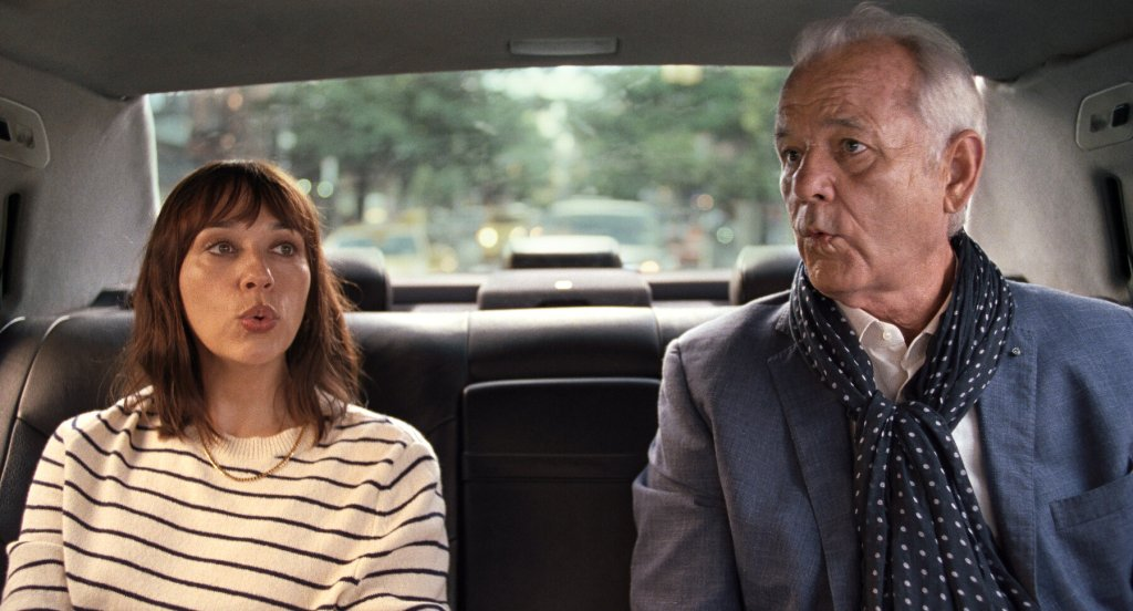 A still from 'On The Rocks'. Laura (Rashida Jones) sits with her father Felix (Bill Murray) in the back of a New York cab. Laura has shoulder length brown hair and bangs, with a white and black striped jumper on. Felix is wearing a linen blue suit jacket with a white shirt and a polka dot scarf, he has grey and thinning hair. The pair are mid-whistle.