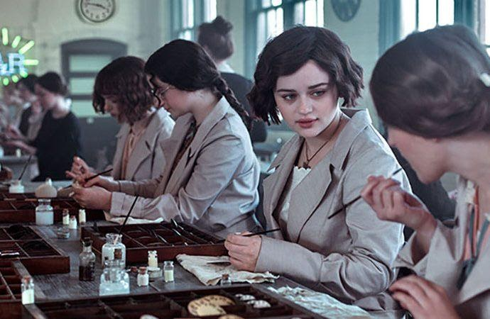 A still from 'Radium Girls'. Bessie (Joey King) is shown working in lab coats with three other women. It is the 1920s and they are painting with radium in a workhouse. Bessie is turning to the woman on her left and watching as she touches a paintbrush to her lips.
