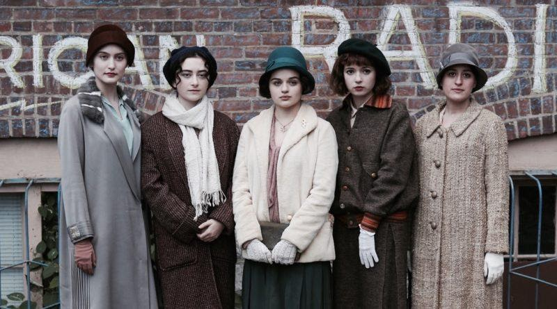 A still from 'Radium Girls'. Bessie (Joey King) stands in the centre of the image flanked by two women either side of her, other 'Radium Girls' working with the deadly material. They are all in 1920s winter fashions, long neatural coloured coats and cloche hats, all women are wearing gloves. They are standing in front of a graffitied wall as if having their picture taken for a newspaper.