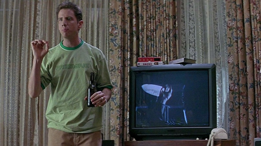 A still from 'Scream'. Randy Meeks (Jamie Kennedy) stands to the left of the frame, in mid shot, next to a TV. Some ugly floral and lace curtains are behind him. A slasher movie plays on the TV. Randy is a young white man in his 20s, he has short brown hair in a crew cut, spiked up with gel. He wears a green ringer t-shirt and tan cargo pants. He holds a drink in one hand and is holding up his left arm in explanation.