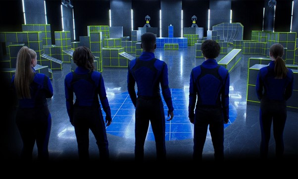 A still from 'Secret Society of Second-Born Royals'. A group of 5 teenagers, 3 girls and 2 boys, stand with their backs to camera. They all wear scuba tops in blue and black with black trousers. They are standing in a large room/warehouse with lots of grids and blocks scattered around the floor in grey colouring with yellow borders.