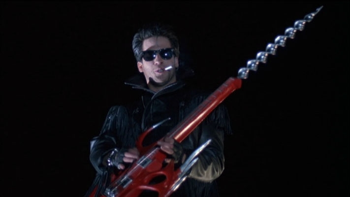 A still from 'Slumber Party Massacre 2'. The Driller Killer is shown centre frame, mid shot, shot from below. The image is black apart from his presence. He is a biker, rocker type with a fringed leather jacket, slicked back hair, black Ray Bans, cigarette in his mouth holding a custom bright red guitar with drill bit on the end where the tuning dials would be.