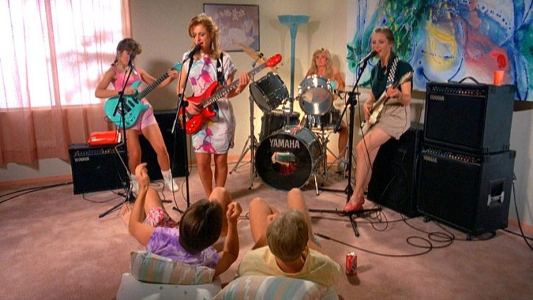 A still from 'Slumber Party Massacre 2'. Courtney (Crystal Bernard) is in a very pink twinged living room shown in a wide shot rehearsing with her 4 piece band, all women, of which she is the singer and guitarist. Two male friends sit in the floor on beanbags looking on. The girls are dressed in full 80s clothing in bright colours.