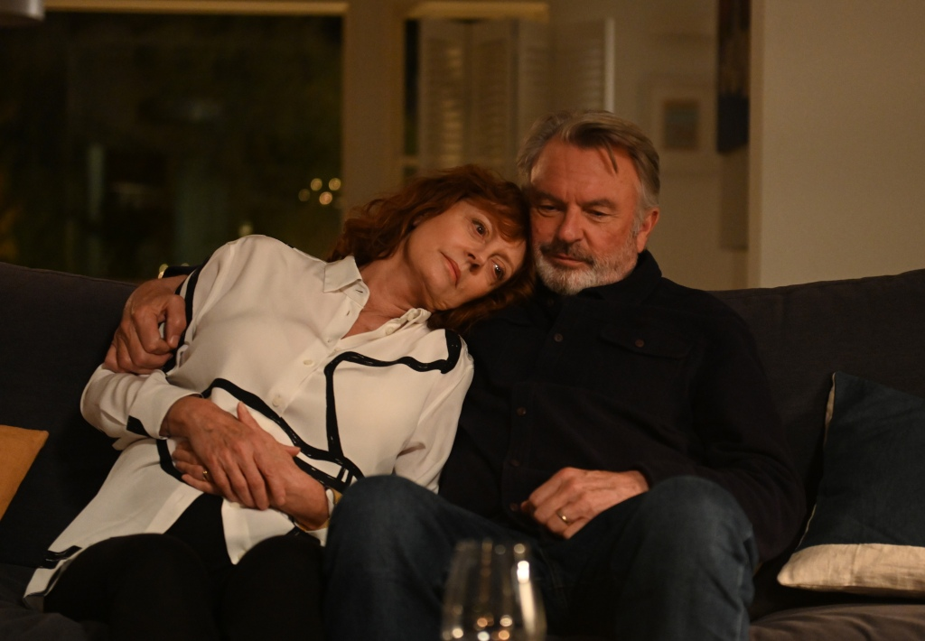 A still from 'Blackbird'. Lily (Susan Sarandon) and Paul (Sam Neill), a 70-something couple, sit on their sofa in their beachside home. Lily wears a white shirt with black detailing and rests her red-haired head on Paul's shoulder. Paul has a greying beard and wears a navy shirt,