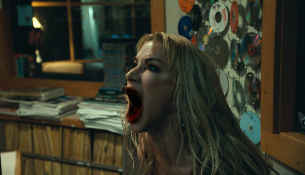 A still from 'Ten Minutes to Midnight'. Radio host Amy Marlowe (Caroline Williams) is in her studio full of records and CDS. She is shown in close-up, profile view. She is screaming and her mouth is wide open and full of blood. She has long blonde hair and heavy makeup.