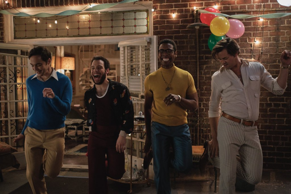 A still from 'The Boys in the Band'. Michael (Jim Parsons), Emory (Robin de Jesus), Bernard (Michael Benjamin Washington) and Larry (Andrew Rannells) are dancing out on the patio of an Upper East Side flat. They are all smiling and in motion, flamboyant looking and well dressed in 1960s/70s clothing.