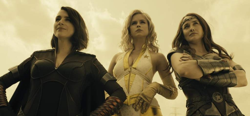 A still from 'The Boys' Season2. Stormfront (Aya Cash), Starlight (Erin Moriarty) & Queen Maeve (Dominique McElligott) are shown standing together in mid-shot, shot from below. They are all superheros in various spandex, leather and armour designs. Stormfront and Queen Maeve are both in dark colours and Starlight wears white and gold.
