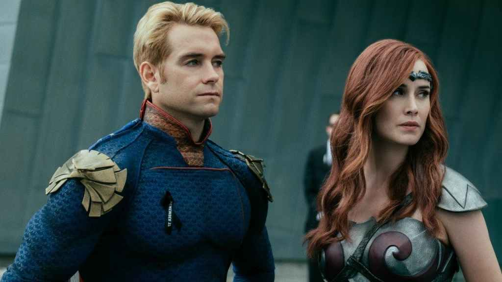 A still from 'The Boys' Season 2. Homelander (Antony Starr) stands next to Queen Maeve (Dominique McElligott). They are pictured in close-up, looking to their right. Homelander is wearing a blue sueprhero suit with eagle epaulets on his shoulders and a red collar. His hair is blonde and his expression concerned. Queen Maeve has a armour-based superhero costume in silver with red detailling and a circlet headband. She has waved, long red hair.