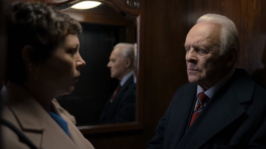 L to R - Olivia Colman and Anthony Hopkins in an wood-paneled elevator with a medium sized mirror mounted on the wall.
